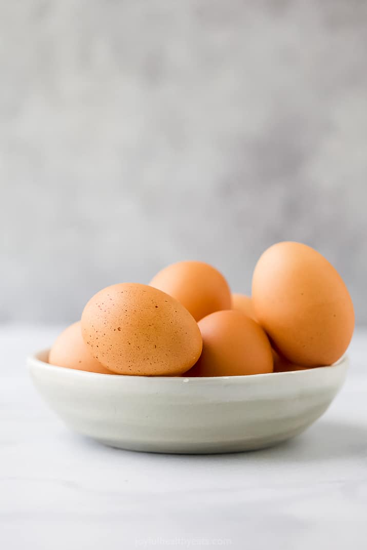 Side view of a bowl of raw brown eggs in a shallow bowl