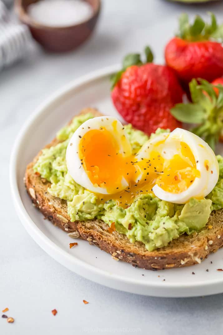Close-up of smashed avocado toast topped with a soft-boiled egg served with fresh strawberries on a plate