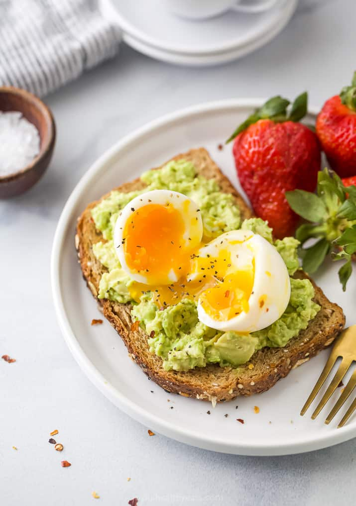 Overhead view of a plate of smashed avocado toast topped with a soft boiled egg served with fresh strawberries
