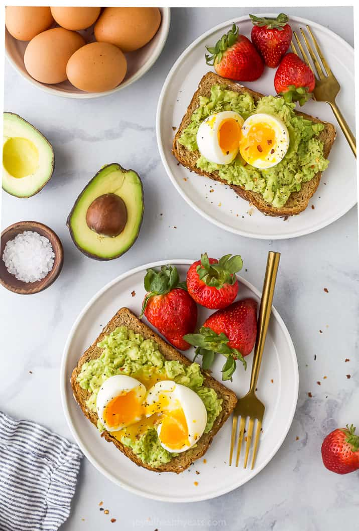 Overhead view of two plates of smashed avocado toast topped with a soft-boiled egg and served with fresh strawberries
