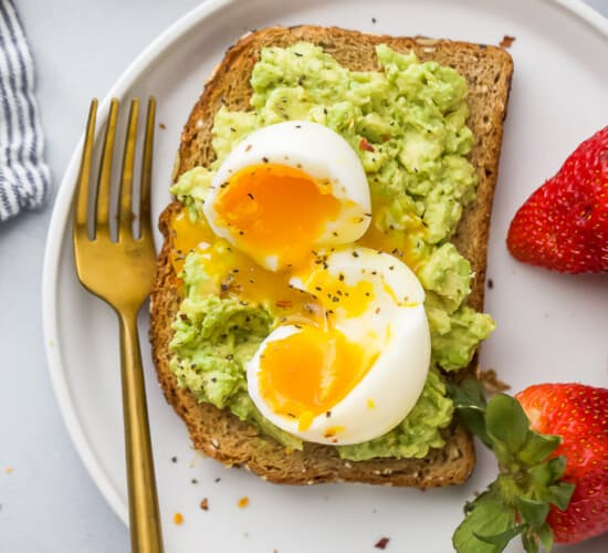 Close-up overhead view of smashed avocado toast topped with a soft-boiled egg served with fresh strawberries