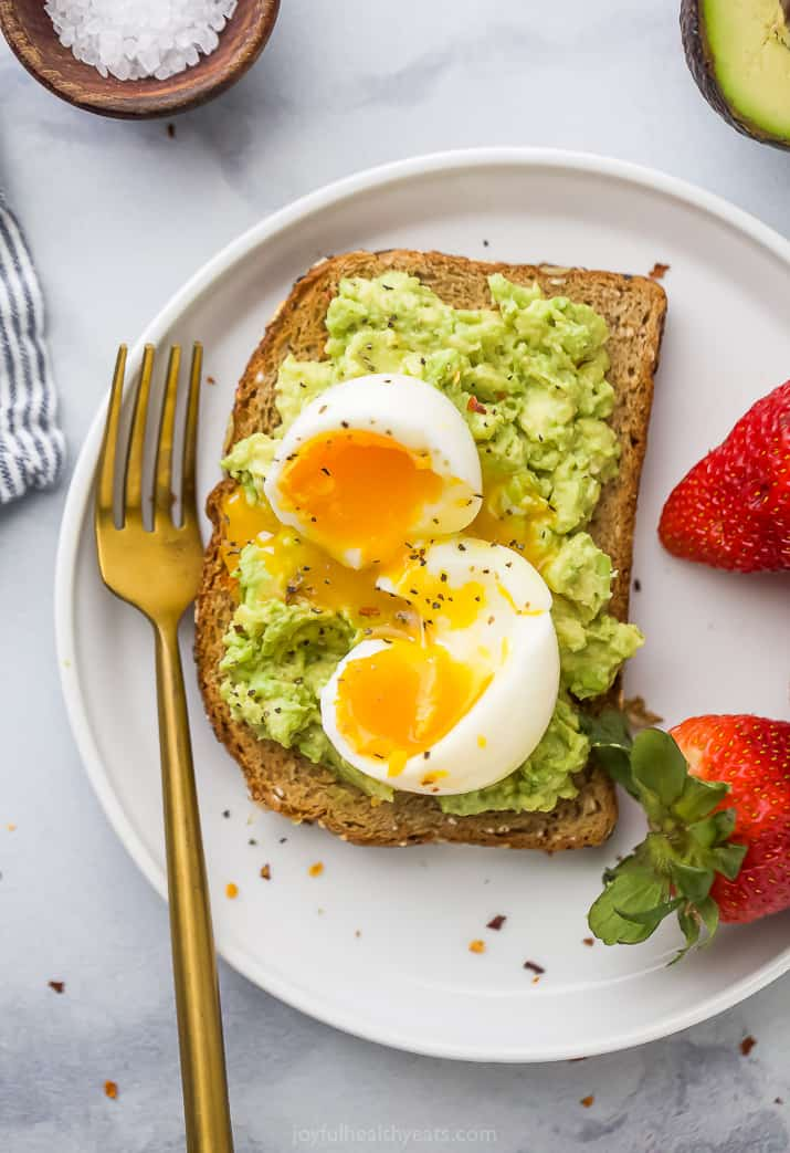 Overhead view of a plate with smashed avocado toast topped with a soft boiled egg served with fresh strawberries