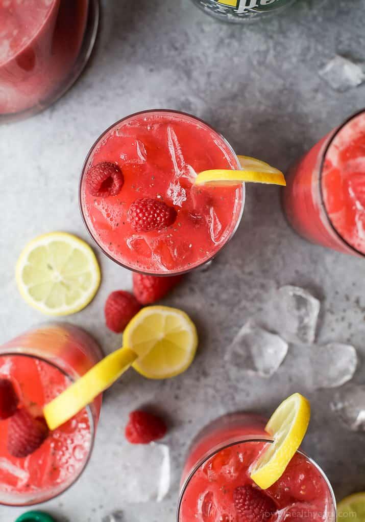 Top view of glasses of Chia Raspberry Lemonade Spritzer with fresh lemon and raspberry garnish
