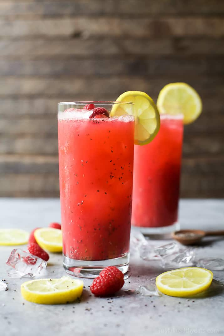 Two tall glasses of Chia Raspberry Lemonade Spritzer garnished with lemon slices