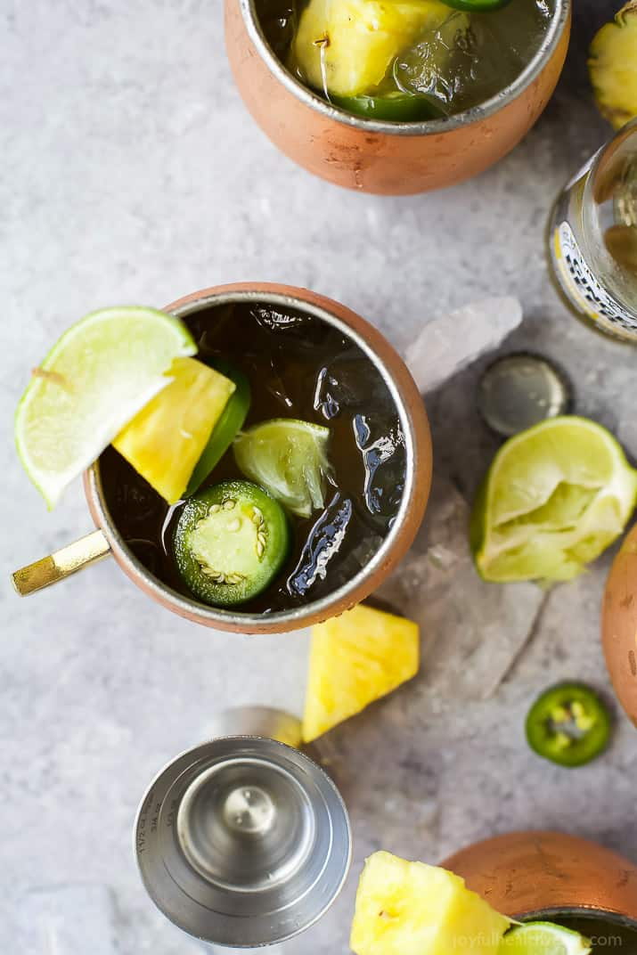 Top view of a Jalapeno Pineapple Moscow Mule with limes, pineapple and jalapenos on a table