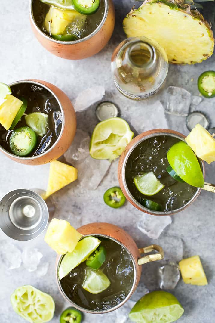 Top view of four Moscow Mules in copper cups surrounded by pineapple, limes, ice and jalapenos
