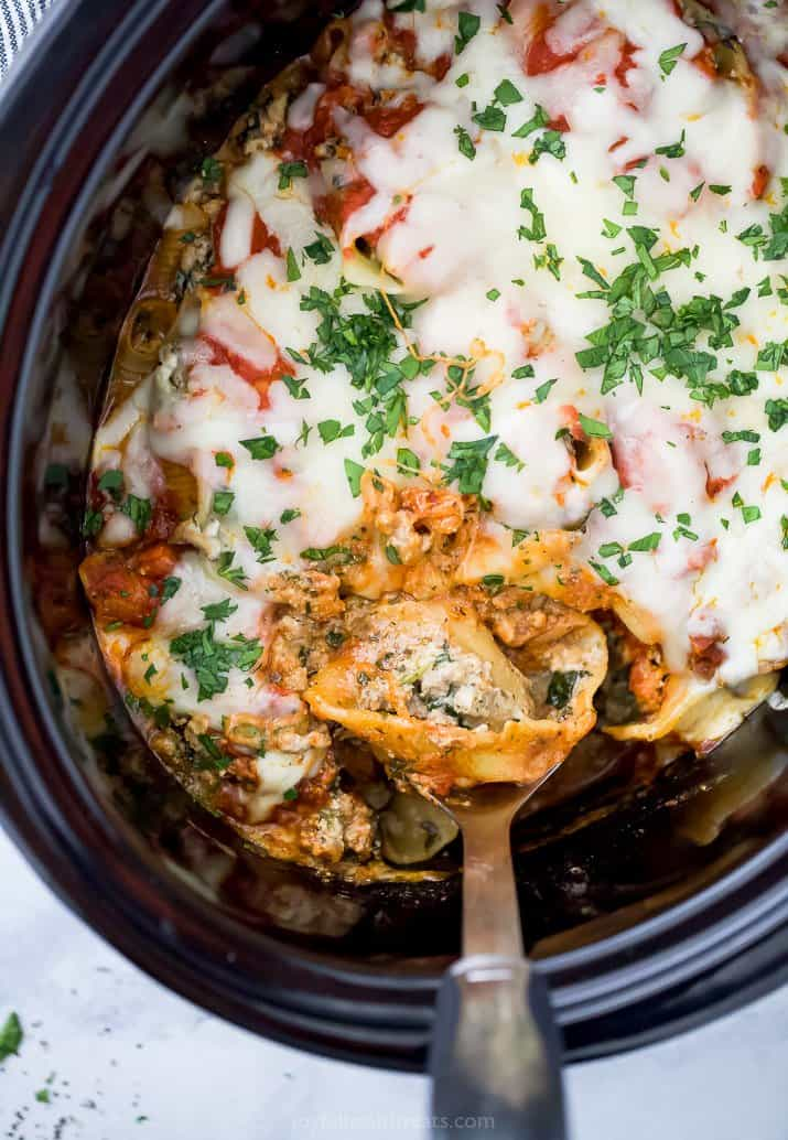 a spoon in a crock pot filled with stuffed shells