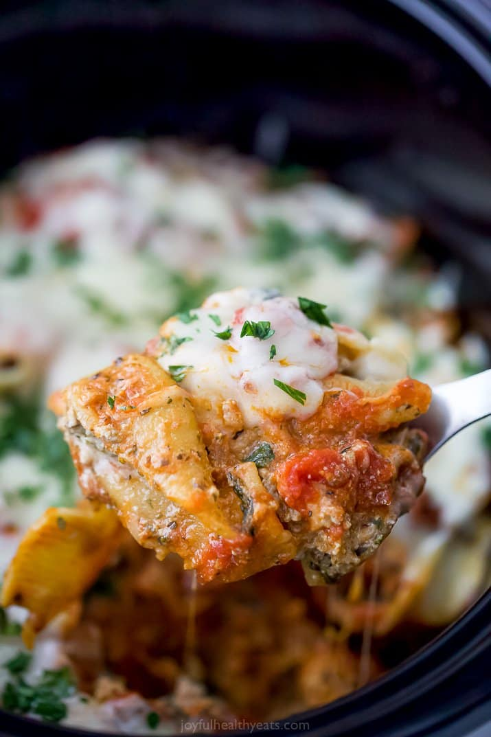 a spoon scooping stuffed shells from a crock pot