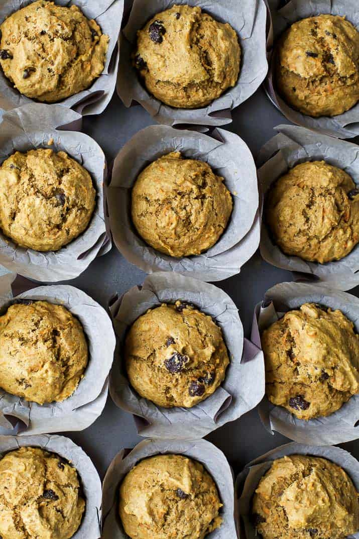 Top view of a dozen Healthy Carrot Cake Muffins in parchment wrappers
