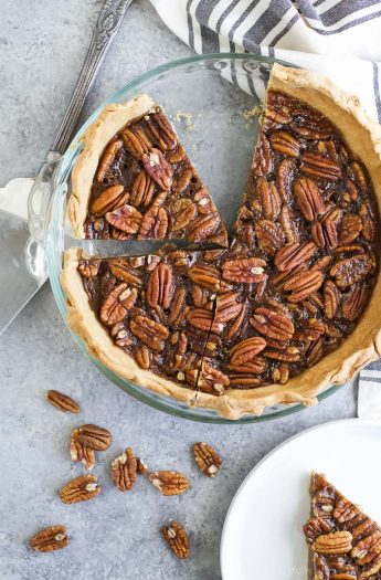 A Pecan Pie in a pie dish with a slice taken out.