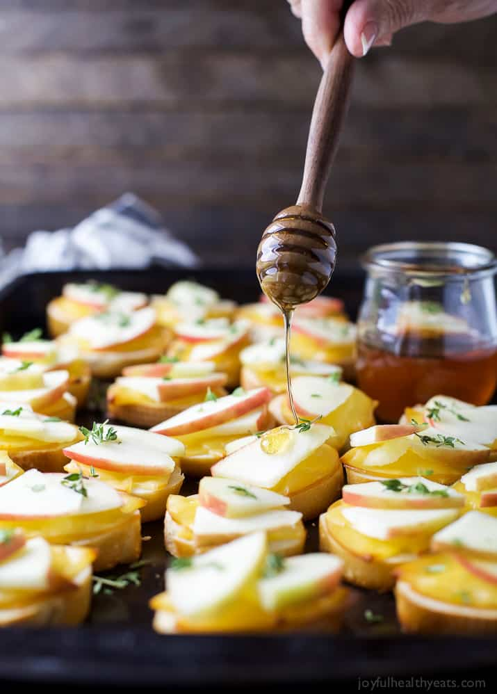 A Pan of Smoked Gouda and Apple Crostini Being Drizzled with Honey