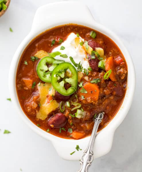 a crock bowl filled with beef chili and toppings