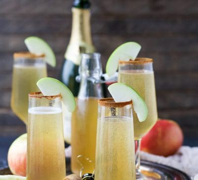Easy 2 ingredient Apple Cider Mimosas - you'll love this fall twist on a classic mimosa. These Apple Cider Mimosas are the perfect bubbly cocktail to start off your holidays!