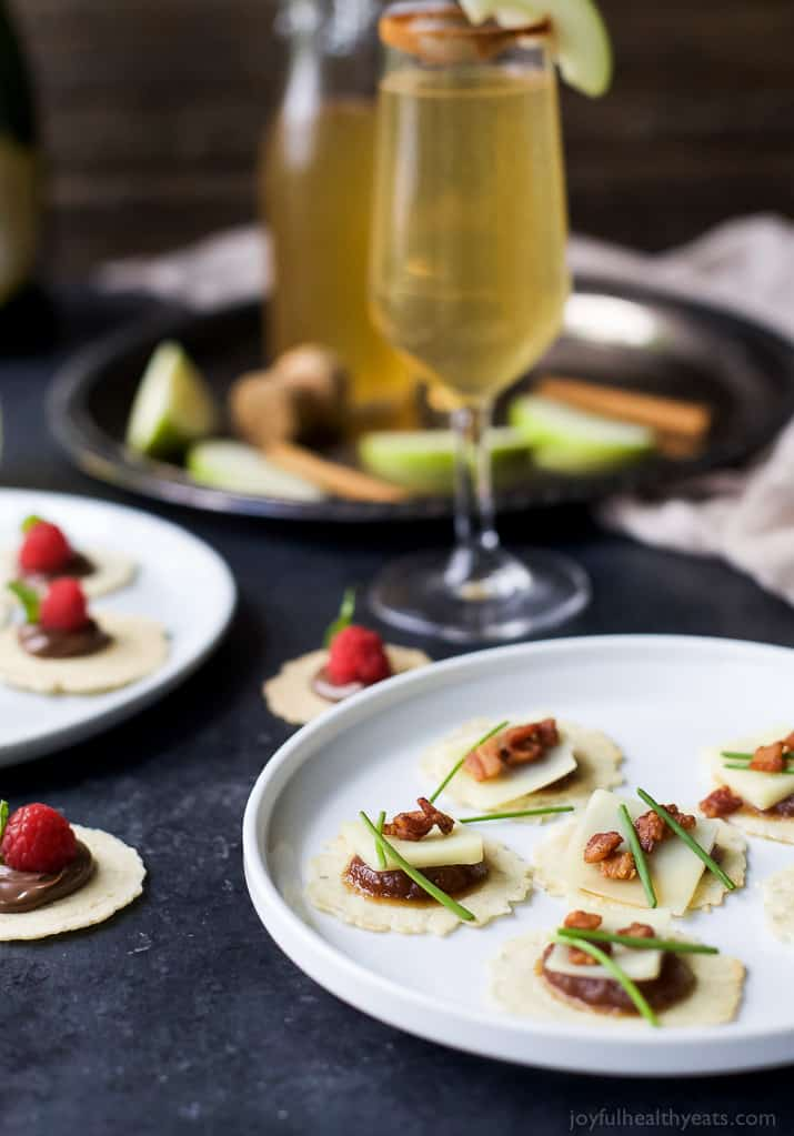 A Plate of Savory Appetizer Bites Beside a Glass of Champagne and a Plate of Sweet Bites