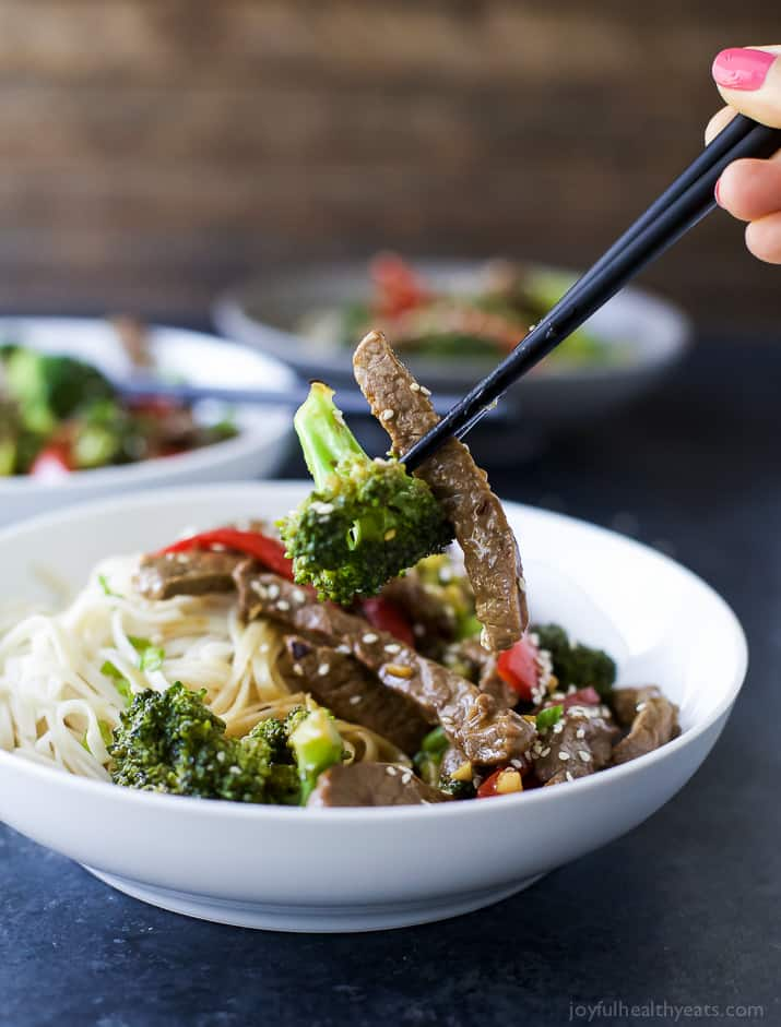 Chop sticks grabbing Beef and Broccoli Stir Fry with noodles in a bowl