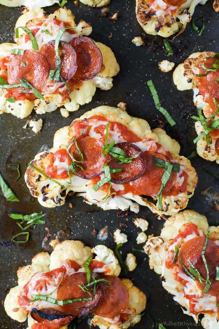 Top view of Cauliflower Steak Pepperoni Pizzas on a baking sheet