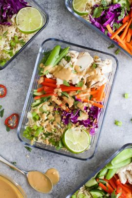 thai chicken grain bowls in a pyrex container drizzled with peanut dressing