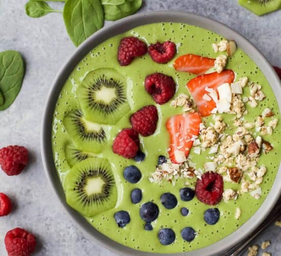 A Green Smoothie Bowl topped with fresh fruit and granola.