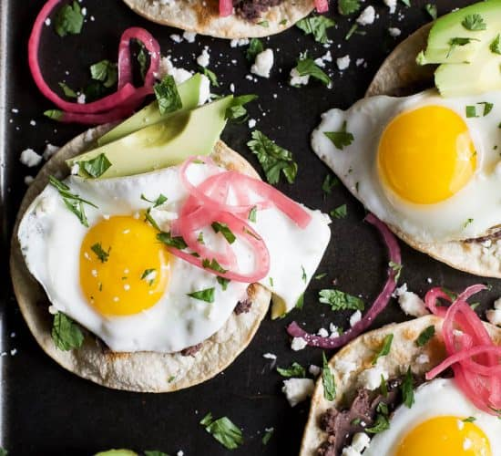 Healthy Huevos Rancheros Breakfast Tostadas topped with creamy avocado and pickled onions. These breakfast tostadas are a delicious breakfast option that are high in protein and fiber with only 292 calories a serving!