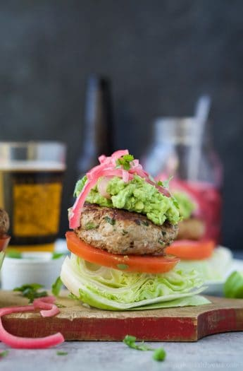 Healthy Paleo Chipotle Turkey Burgers filled with tex-mex flavor then topped with zesty guacamole and pickled onions. These Turkey Burgers are low carb, high in protein, done in 30 minutes and guaranteed to be a favorite!