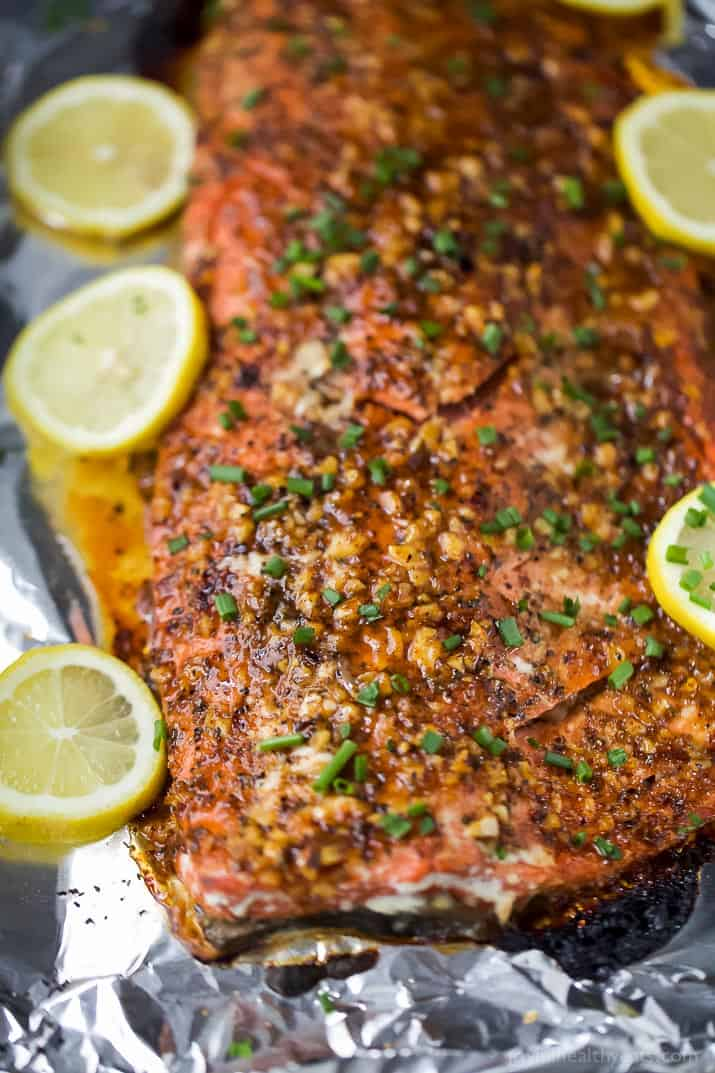 Easy Paleo Honey Mustard Baked Salmon in tin foil for easy cleanup. This sweet and spicy Baked Salmon is less than 200 calories, high in protein and done in less than 30 minutes!