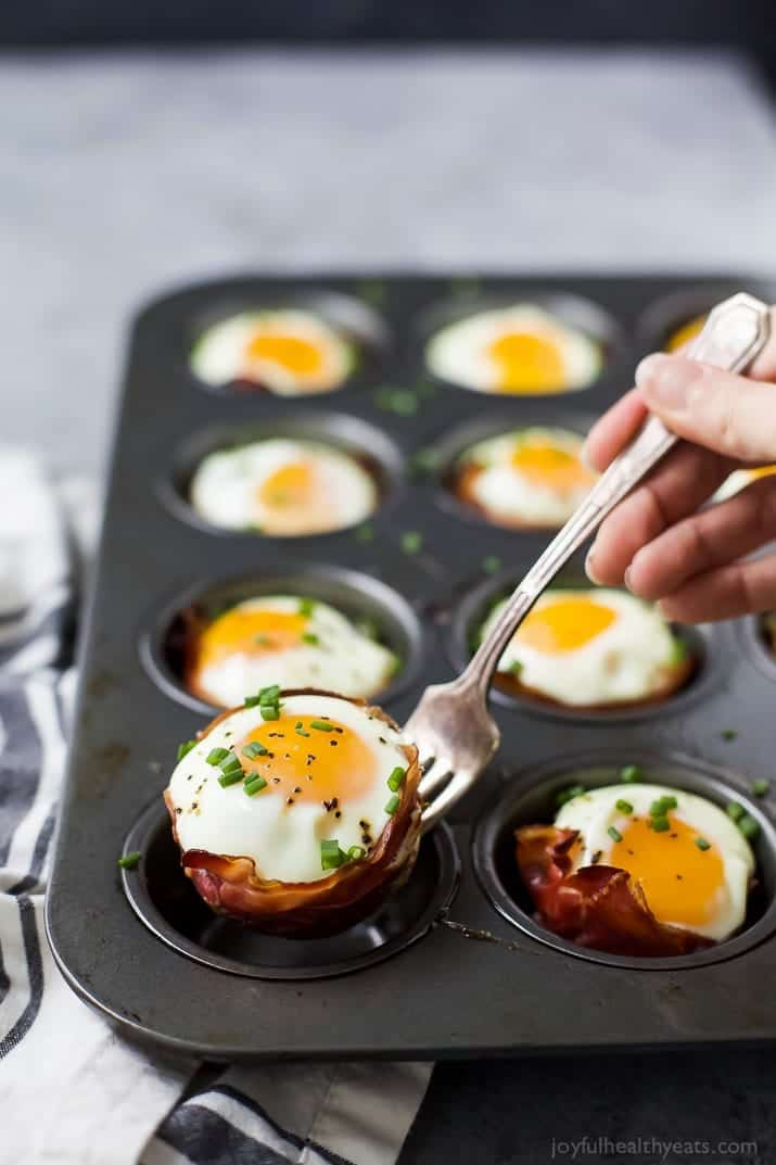 PROSCIUTTO BAKED EGG CUPS in a muffin tin with one being picked up with a fork