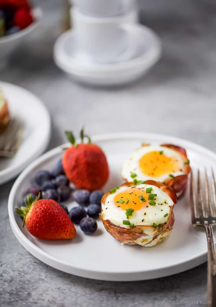 PROSCIUTTO BAKED EGG CUPS with fresh fruit on a plate