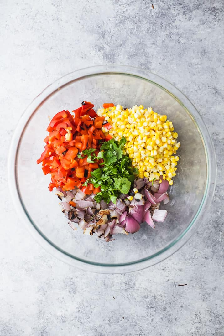 Chopped vegetables for Charred Corn Roasted Red Pepper Farro Salad in a mixing bowl