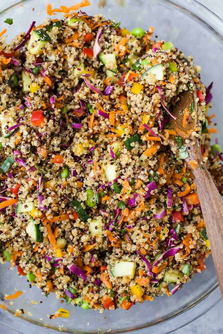 Top view of Crunchy Thai Quinoa Salad in a mixing bowl with a wooden spoon