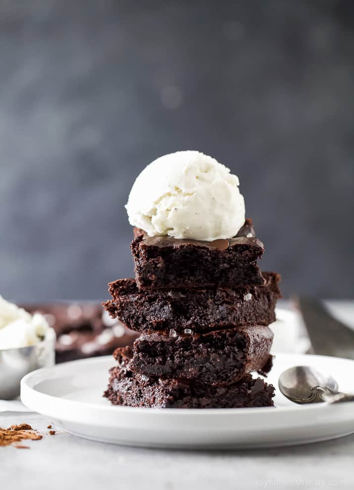 A stack of fudgy almond butter brownies with a scoop of vanilla ice cream on top