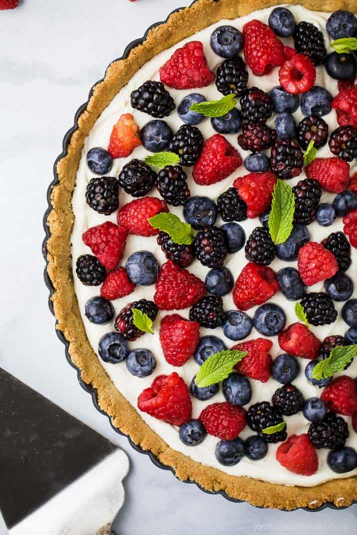 Top view of a Berry Tart filled with a creamy greek yogurt cheesecake filling and an Almond Crust