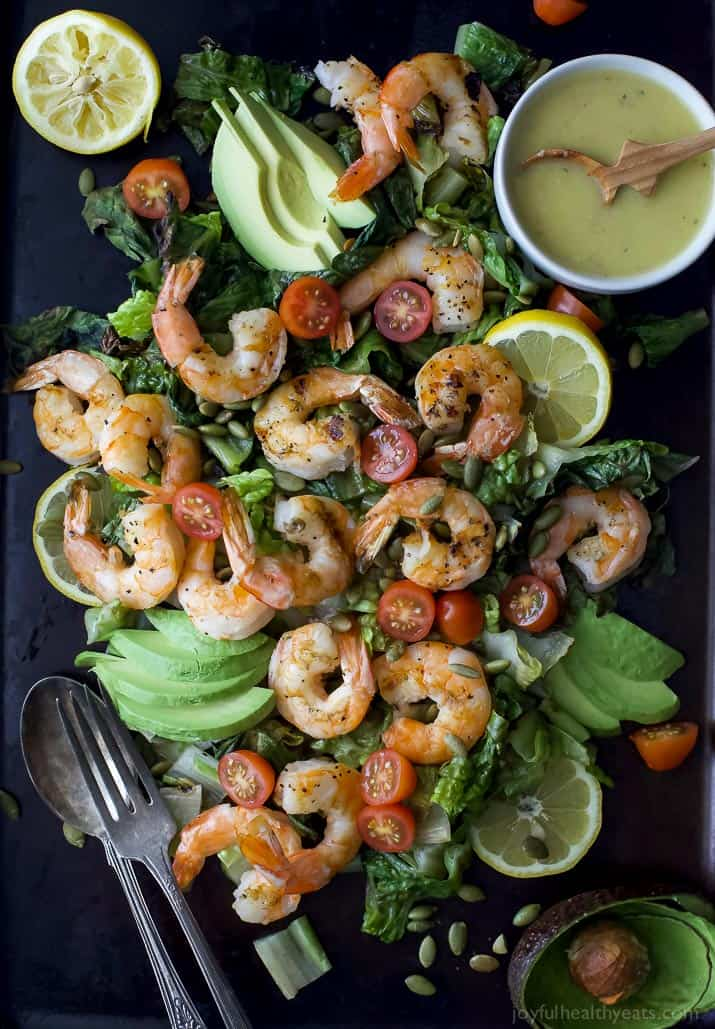 Top view of Grilled Shrimp Caesar Salad with sliced avocado and homemade Caesar dressing
