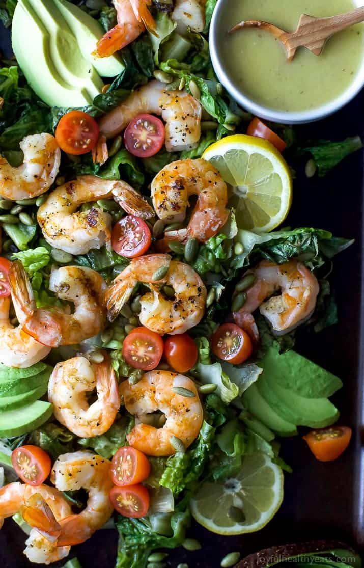Top view of Grilled Shrimp Caesar Salad with a bowl of homemade Caesar dressing