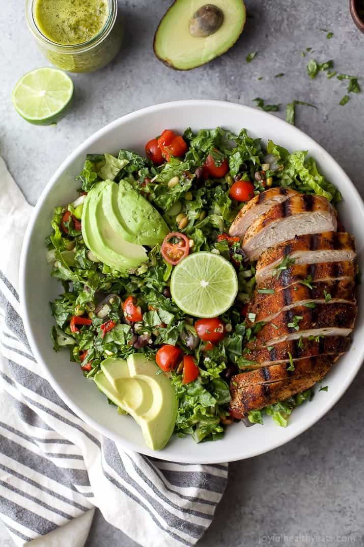 A large white bowl filled with Mexican Chopped Salad with grilled chicken and avocados