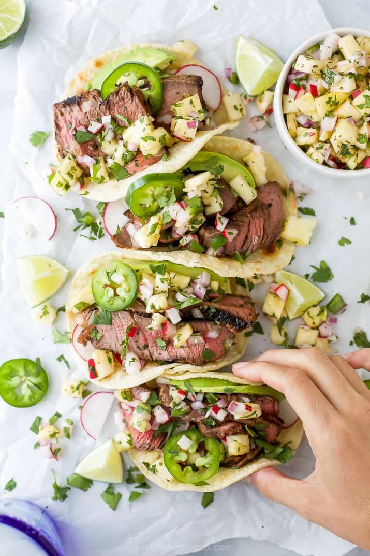 hand grabbing steak tacos with pineapple salsa