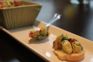 A Piece of Avocado Bruschetta on a Serving Plate with More Bruschetta in a Spoon