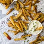 These Crispy Oven Baked Fries served with a Roasted Garlic Aioli make the perfect side dish for summer. These homemade french fries are baked instead of fried for a guilt free bite that can be served with anything!