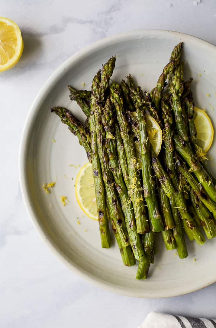 Grilled Asparagus topped with fresh Lemon zest on a plate