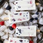 Paleo Berry Coconut Popsicles a sweet refreshing summer treat that's easy to make! These creamy Coconut Popsicles are filled with tart berries and finished with a vanilla bean coconut mixture. They'll be a hit all summer long!