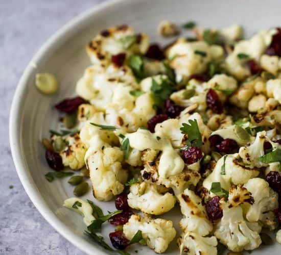 Roasted Cauliflower Salad tossed with a Curry Yogurt Sauce, dry cranberries and pepitas! This healthy salad is easy to make and loaded with flavor! It's the perfect side dish to bring to your next party - definitely a conversation starter.