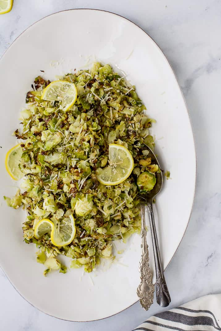 Garlic Parmesan Roasted Brussels Sprouts make a quick easy side dish the family will love. These Brussels Sprouts are tossed with shredded parmesan, loads of garlic and fresh lemon juice for one delicious gluten free recipe!