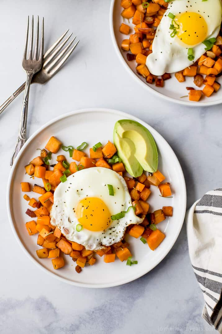 paleo sweet potato hash & eggs on a plate with an avocado
