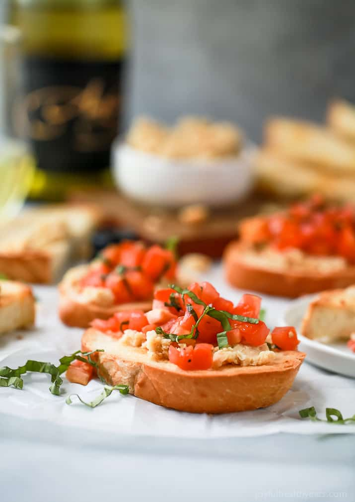 Smashed Chickpea Crostini topped with a fresh tomato Bruschetta - a light vegetarian appetizer perfect for the summer!