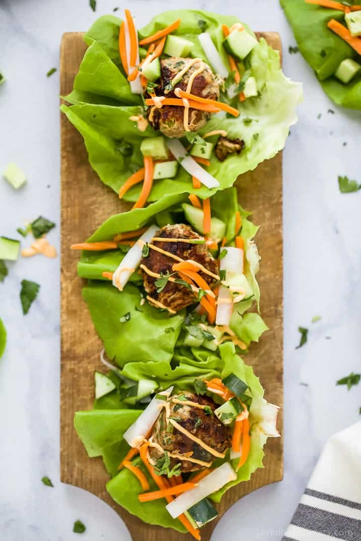 Top view of three Banh Mi Lettuce Wraps with turkey meatballs served on a lettuce wrap with pickled vegetables and sriracha mayo