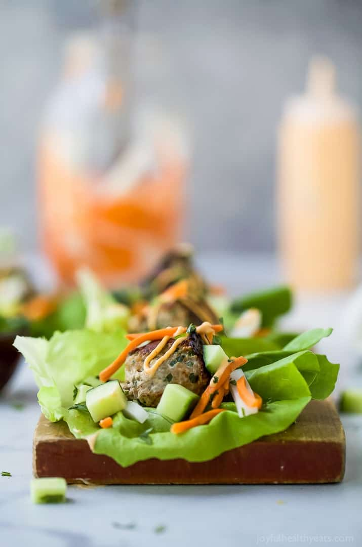 Close-up view of a Banh Mi Lettuce Wrap on a wooden board with turkey meatballs served on a lettuce wrap with pickled vegetables and sriracha mayo