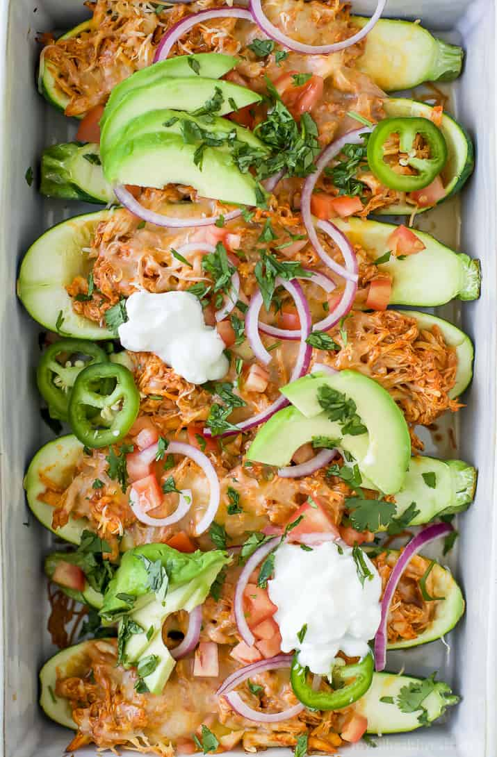 Top view of Chicken Enchilada Zucchini Boats in a baking dish topped with avocado, red onion, sour cream and fresh herbs