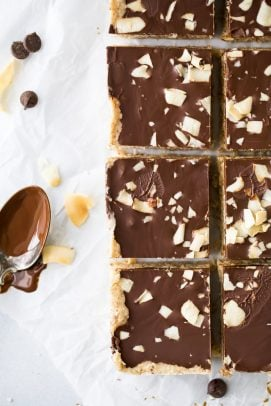 healthy no bake almond joy bars with a spoon of chocolate next to them