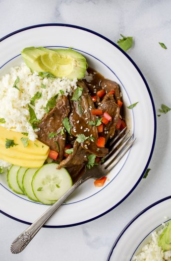 Instant Pot Korean Beef Bowls, a 30 minute meal with tender beef cooked in a sweet spicy korean sauce. This easy instant pot recipe is served on a bed of cauliflower rice with mango and avocado! Guaranteed to be a hit! #glutenfree