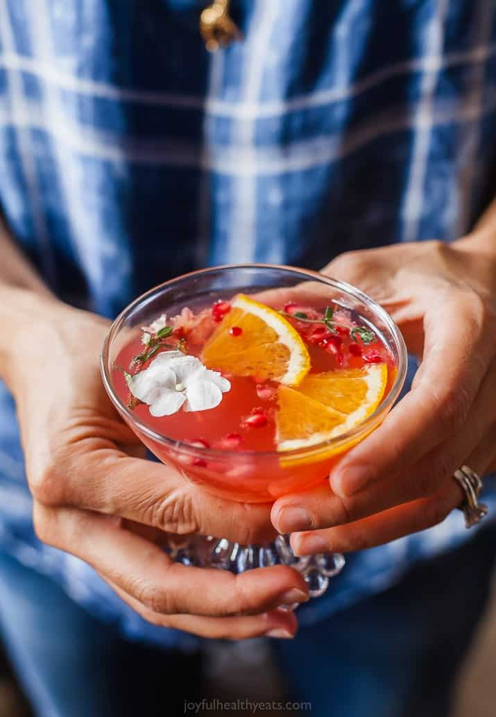 photo of someone holding a glass of holiday pomegranate gin cocktail