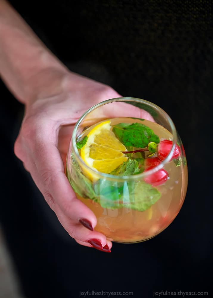 photo of a hand holding a glass of lime mint kombucha cocktail